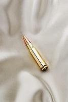 Bullet laying on satin pillow