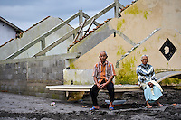 A couple sitting on the remains of a house partially buried by a 'lahar dingin' or 'cold lava' mud flow in March 2011, Sirahan, Magelang, nr Yogyakarta, Java, Indonesia.  They are sitting on the top of a porch protecting the ground floor entrance