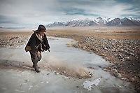 A caravan leader throws earth on the ice, so it is less slippery for the animals. .From Ech Keli to Kyzyl Qorum..Trekking with yak caravan through the Little Pamir where the Afghan Kyrgyz community live all year, on the borders of China, Tajikistan and Pakistan.