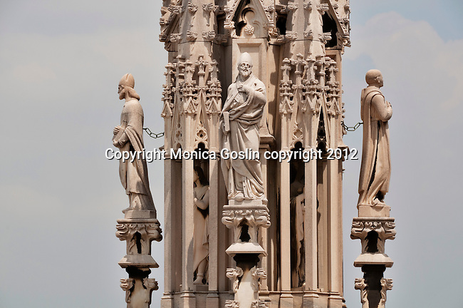 Statues on one of the many spires on the roof of the Duomo in Milan, Italy which is covered in sculptures and carved stone details