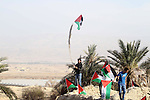 "Palestinian activists hold their national flags at the site of the old village known as Ein Hijleh, in the Jordan valley near the West Bank City of Jericho, January 31, 2014. Hundreds of Palestinians announced today the launching of ""Melh Al-Ard"" (Salt of the Earth) campaign by reviving the village of Ein Hijleh in the Jordan Valley on land belonging to the Orthodox Church and St. Gerassimos monastery. The campaign is launched in refusal of Israeli policies aimed at Judaizing and annexing the Jordan Valley. Photo by Issam Rimawi"