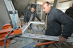 Saeed Elyas Seno (right) a Yazidi displaced from his home village of Bashiqa, Iraq, when the Islamic State group took over the Nineveh Plains in 2014, learns how to fabricate windows and doors from Kheralla Mohammed Hussain, a Muslim who was displaced by the Islamic State group from Mosul, at Hussain's factory in Dohuk. The livelihood training is sponsored by the Christian Aid Program Nohadra - Iraq (CAPNI).