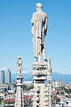 Statues carved on the spires on the roof of the Duomo (Cathedral), look out over the city of Milan, Italy.