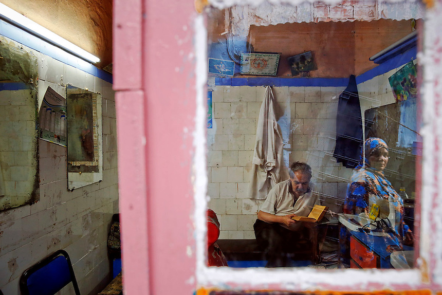 """A woman is reflected in the mirror of shop as a barber reads the Koran in Rabat's Medina September 23, 2014. Behind walls of Medina and Kasbah of the Oudayas, ancient neighbourhoods of Morocco's capital, labyrinths of small alleys, colourful buildings and street markets offer a glimpse into city's rich history. Rabat was recently listed by UNESCO as a World Heritage Site and suggested as a """"must see"""" destination by major media outlets and tourist agencies.  REUTERS/Damir Sagolj (MOROCCO)"""