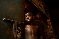 Eight year old Razu works in a rickshaw factory. He earns about 500 taka (7 USD) a month, working 10 hours a day. When the production often stops due to lack of electricity, he has time to play. It is common in Bangladesh for children of poor parents to work in various hazardous and labour-intensive workplaces to support their families. 17.5 percent of all children aged between 5-15 are engaged in economic activities. The average child labourer earns between 400 to 700 taka (1 USD = 70 taka) per month, while an adult worker earns up to 5,000 taka per month..