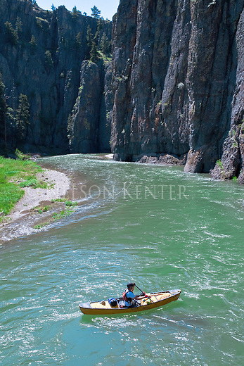 Aqua colors of the Dearborn River in early summer as a canoe paddles toward high rocky cliffs