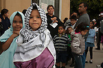 Mexican children dressed as Mary and Joseph lead a community group of all ages from house to house singing Las Posadas in Long Beach, CA