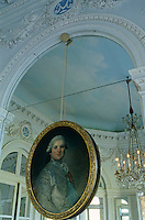 A gilt-framed portrait of the Comte de Provence hangs against a mirrored overmantel which reflects the sky painted on the ceiling above