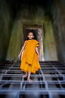 Novice Monk walking through Angkor Wat, Siem Reap, Cambodia