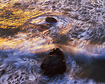 The setting sun highlights the frothing surf below a bluff.