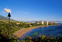Tiki torch above Kaanapali beach and hotels at sunset, West coast, Maui
