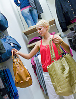Woman looking and comparing different shoulder bags in retail shop. Fashion, store, shopping.