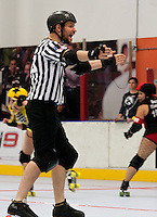 "Cameltron, Back Pack Referee / Head Referee, signals ""Pack Is Here!"" while yelling.  The jammer for the Crash Test Bunnies can be seen racing ahead behind him (thanks to the ""No Pack"" call that preceeded this)."