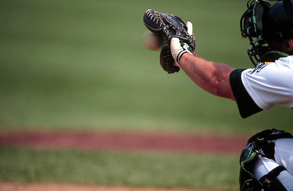 "A baseball catcher ""catches"" the ball as it enters his glove in this undated photo taken in the early 1990's."