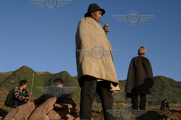 Yi elders wait for a funeral procession to pass.