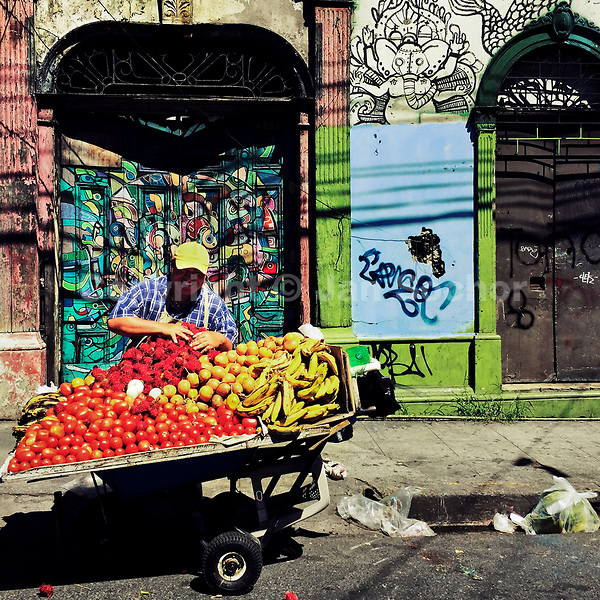 A Salvadoran man sells fruits in front of a ruined house with Spanish colonial architecture elements, painted over by a local artist, in the center of San Salvador, El Salvador, 12 November 2016.