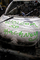 A completely burnt out carwith 'welcome to Hackney' written on it on a street in the London borough of Hackney. London saw the beginnings of riots on Saturday evening, after a peaceful protest in response to the shooting by police of Mark Duggan during an attempted arrest, escalated into violence. By the third night of violence, rioting and looting had spread to many areas of the capital and to other cities around the country.