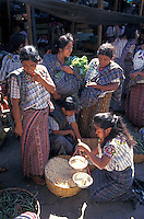 Maya woman wieighing dried corn for a customer in the market in Santiago Atitlan, Guatemala
