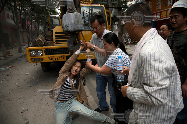 A desperate woman clings onto a vehicle crane in an attempt to have rescue workers extract the body of a relative. An earthquake measuring 7.9 on the richter scale hit Sichuan on 12/05/2008. Rescue workers had given up on finding people alive and began to use heavy machinery.