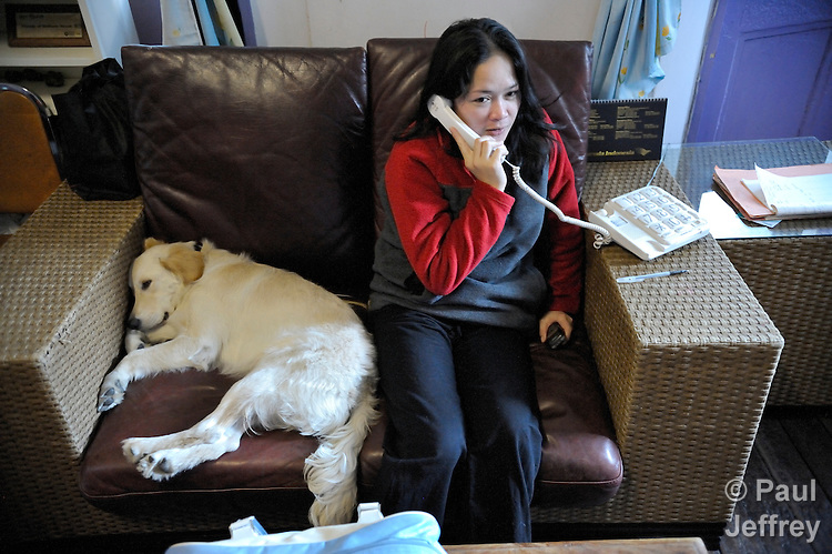 At the Bethune House Migrant Women's Refuge, a ministry with migrant domestic workers in Hong Kong, one of the clients uses the phone accompanied by Summer, the shelter's dog.