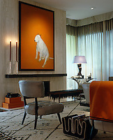 Accents of Hermes orange in this urban living room have taken their inspiration from a large painting of a bull terrier by Ray Richardson displayed above the mantelpiece of the contemporary fireplace
