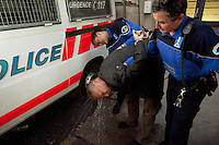 Switzerland. Geneva. A police officer and a policewoman rinse the face of a caucasian man with water at the Paquis police station. The man was arrested because he has refused to pay a prostitute, who sprayed his face as retaliation. The man is completely drunk. A police station or station house is a building which serves police officers and contains offices, temporary holding cells and interview/interrogation rooms.  Pepper spray, also known as OC spray (from &quot;Oleoresin Capsicum&quot;), OC gas, and capsicum spray, is a lachrymatory agent (a chemical compound that irritates the eyes to cause tears, pain, and even temporary blindness) used in policing. Its inflammatory effects cause the eyes to close, taking away vision. 31.03.12 &copy; 2012 Didier Ruef..