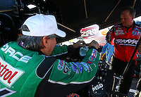 Mar 14, 2014; Gainesville, FL, USA; NHRA funny car driver John Force affixes an in memorial sticker for Ford executive William Clay Ford on the engine of daughter Courtney Force (not pictured) engine during qualifying for the Gatornationals at Gainesville Raceway Mandatory Credit: Mark J. Rebilas-USA TODAY Sports