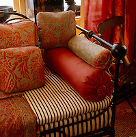 Damask bolsters and cushions decorate this wrought-iron daybed, with a black and white striped mattress