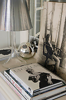 A detail of a side table in the living room displaying an acrylic lamp with a silver metallic shade and a collection of postcards, photographs and books
