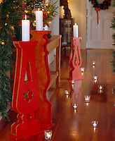 Tea lights in tiny glasses are arranged on the wooden floor in this hallway which is decorated for Christmas