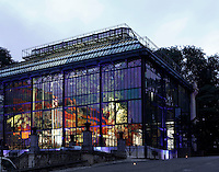 Plant History Glasshouse (formerly Australian Glasshouse), 1830s, Rohault de Fleury, Jardin des Plantes, Museum National d'Histoire Naturelle, Paris, France. Low angle view showing the glass and iron structure on a midsummer evening with the interior illuminated to show the luxuriant plants growing there.