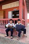 Bunroeun sits outside the school with a friend. they both have violin cases. He is taught classical violin at the Phnom Penh school of 'Beaux Arts' outside Phnom Penh..A Khmer boy learns to play classical violin at the school of Beaux Arts, at the edge of Cambodia's capital, Phnom Penh. He is an orphan and comes from a poor family. His parents died long ago, from AIDS related diseases. He lives with his grandmother and his uncle, and their family. He lives on the top floor of an apartment block, where his family run a textile business, sewing together clothes and ornamental flags from around the world. A dozen young women work in this textile business, and the boy's home space is actually amidst this small factory environment which he shares with them. They eat, work and play together like an extended family or community. Phnom Penh, Cambodia
