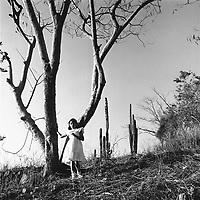 A Mexican girl climbs down a hillside in her beautiful white dress in Buena Vista de Cuellar, Mexico.