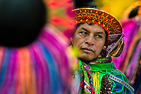"""A Colombian Kamentsá native, wearing a colorful headgear, takes part in the Carnival of Forgiveness, a traditional indigenous celebration in Sibundoy, Colombia, 12 February 2013. Clestrinye (""""Carnaval del Perdón"""") is a ritual ceremony kept for centuries in the Valley of Sibundoy in Putumayo (the Amazonian department of Colombia), a home to two closely allied indigenous groups, the Inga and Kamentsá. Although the festival has indigenous origins, the Catholic religion elements have been introduced and merged with the shamanistic tradition. Celebrating annually the collaboration, peace and unity between tribes, they believe that anyone who offended anyone may ask for forgiveness this day and all of them should grant pardons."""