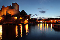 Chateau Royal and the harbour, Collioure, France, seen at night with the street lights reflecting in the sea. Much of the castle was built in the 13th and 14th centuries by the Dukes of Roussillon and the Knights Templar. In the 16th century Collioure was under Spanish control and Philip II modernised and reinforced the castle. It was taken by the French in 1659 after which the bastions were built by Vauban (1633-1707). Picasso, Matisse, Derain, Dufy, Chagall, Marquet, and many others immortalized the small Catalan harbour in their works. Picture by Manuel Cohen.