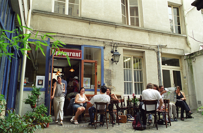 The outside seating terrace in the back yard. Wine bar les Enfants Rouges in Paris. Paris, France.