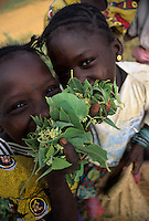 Near Niamey, Niger. Fulani Girls Gathering Leaves for Food, to be mixed in stews and sauces.  Note the facial tattoos and scarification.