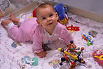 Six month old baby in play pen with toys looking up at camera smiling Lynnwood Washington State USA   MR