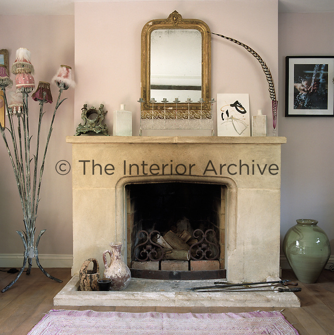 In the living room an antique gilt-framed mirror hangs above the pale stone fireplace