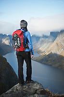 Female hiker takes in view of dramatic mountain landscape from Reinebringen, Lofoten Islands, Norway