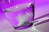 An effervescent tablet dissolves in a glass of water against a purple background. Royalty Free