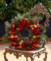 An autumn themed wreath with roses, crab apples and berries resting on a carved chair
