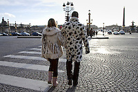 Pedestrians in winter coats walking across cobbled road on zebra crossing in Place de la Concorde, Central Paris, France