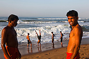 Young men seen playing on the beach along the Bay of Bengal in Puri, Orissa, India. A dip in its salty waters is believed to hold great religious significance, as a result these golden sand beaches sees is a never-ending rush of pilgrims and tourists. Photo: Sanjit Das/Panos