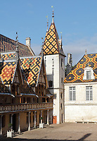 Les Hospices de Beaune, or Hotel-Dieu de Beaune, a charitable almshouse and hospital for the poor, built 1443-57 by Flemish architect Jacques Wiscrer, and founded by Nicolas Rolin, chancellor of Burgundy, and his wife Guigone de Salins, in Beaune, Cote d'Or, Burgundy, France. The buildings, set around an internal courtyard, are in Northern Renaissance and Flamboyant Gothic style, with half-timber galleries, ornate rooftops with Burgundian glazed tiles in geometric patterns and dormer windows. The hospital was run by the nuns of the order of Les Soeurs Hospitalieres de Beaune, and remained a hospital until the 1970s. The building now houses the Musee de l'Histoire de la Medecine, or Museum of the History of Medicine, and is listed as a historic monument. Picture by Manuel Cohen