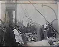 BNPS.co.uk (01202) 558833<br /> Picture: HAldridge/BNPS<br /> <br /> ****Please use full byline****<br /> <br /> A haunting, never-before-seen photo showing victims of the Titanic disaster being buried at sea has been discovered 101 years on.<br /> <br /> The black and white snap was taken on board one of the body recovery ships during a mass funeral service of dozens of the dead.<br /> <br /> The image, that shows body bags stacked on the windswept deck while two crewman tip up a stretcher to drop a victim over the side, is to sell at auction at Henry Aldridge and Sons in Devizes.
