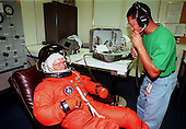 STS-95 Payload Specialist John H. Glenn Jr., a U.S. Senator from Ohio and one of the original seven Project Mercury astronauts, suits up with the help of George Brittingham,  United Space Alliance, in the Operations and Checkout (O&C) Building prior to his trip to Launch Pad 39-B on October 9, 1998. Glenn and the rest of the STS-95 crew are at KSC to participate in the Terminal Countdown Demonstration Test (TCDT) which includes mission familiarization activities, emergency egress training, and a simulated main engine cutoff.  Following the TCDT, the crew will be returning to Houston for final flight preparations..Credit: NASA via CNP