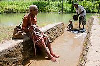 An elderly Indonesian man along a river dam