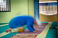 A timed exposure of a  Muslim man praying.