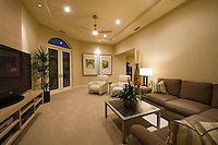 View inside family room with large flat scren TV in foreground and arched French door in background
